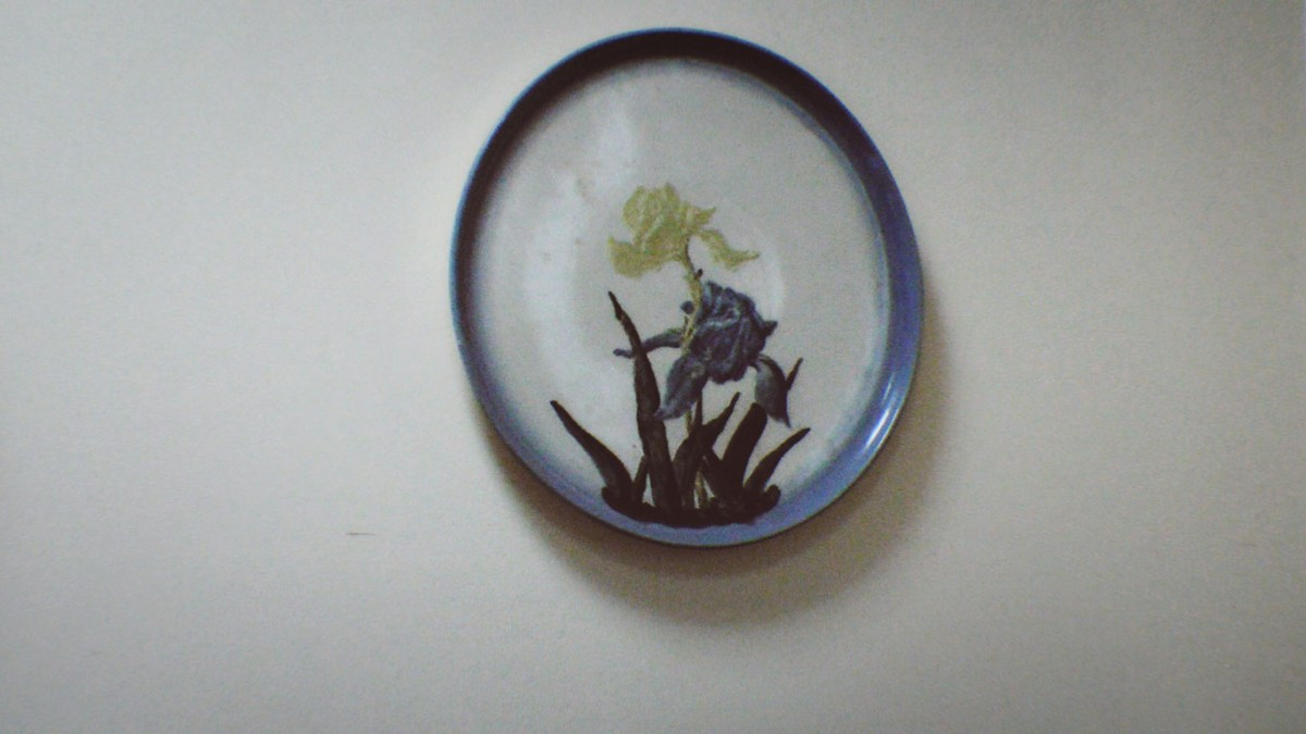 Image of a hanging ceramic plate with blue border and a yellow iris and blue iris.