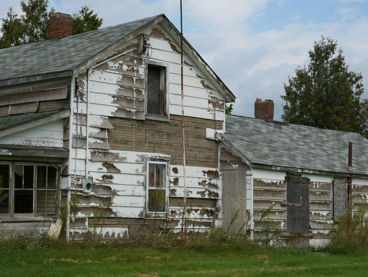 Image of old wooden house with peeling white paint.