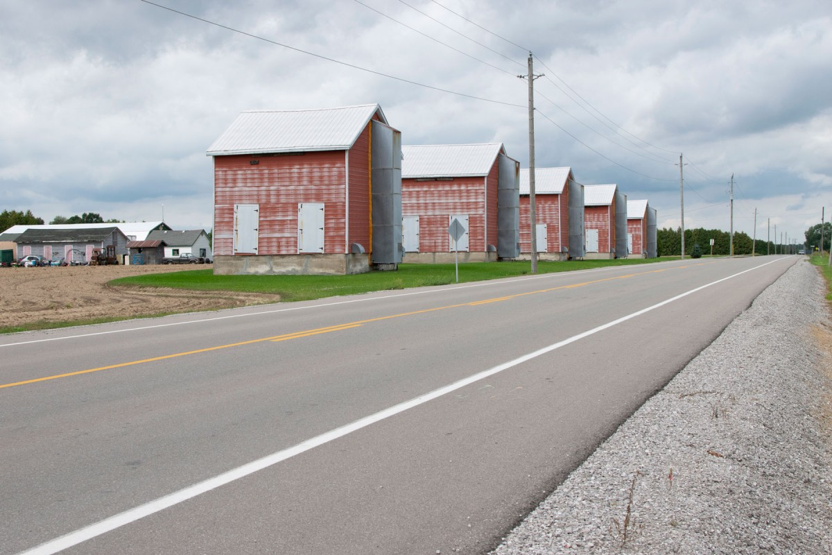 Image of a highway with rows of brick coloured barns.