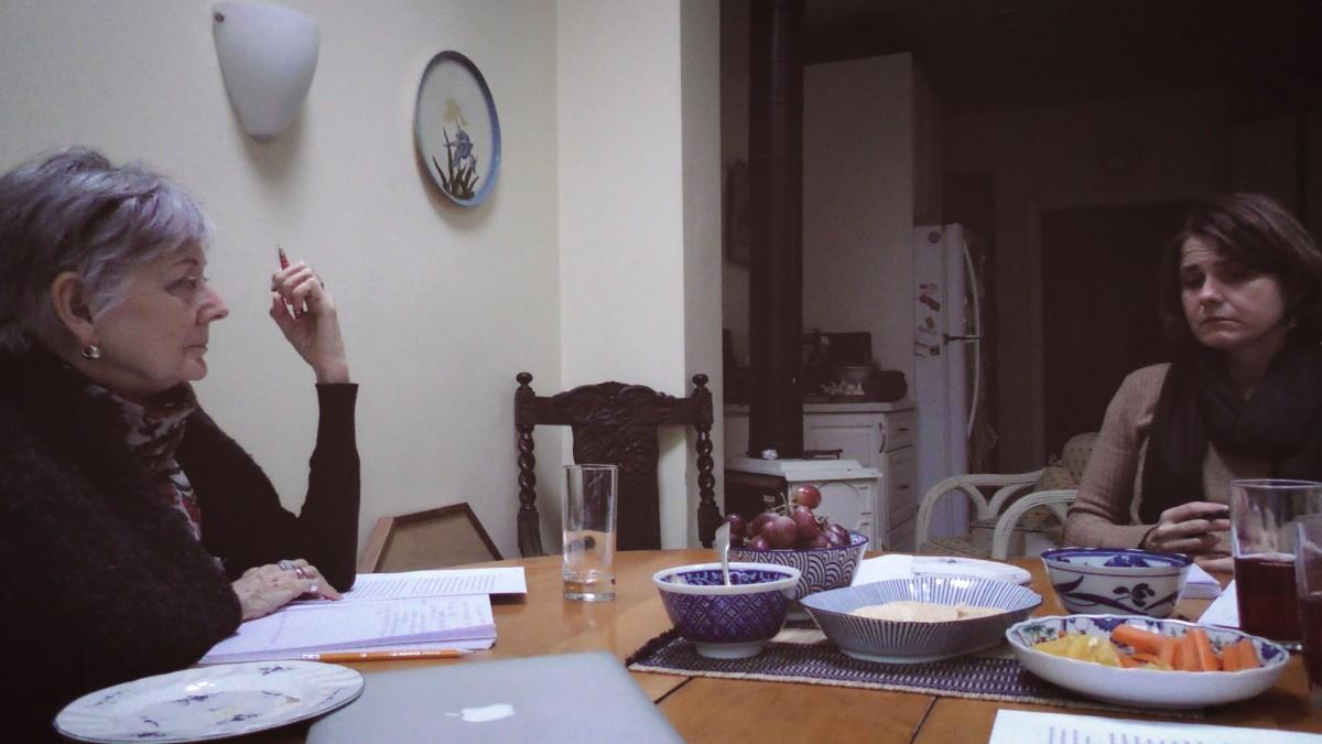 Image of Lynn Hutchinson Lee and Magdalena Kazubowski Huston sitting and talking at a wooden table.