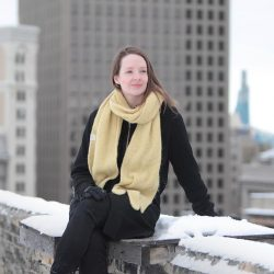 Image of Associate Freya Björg Olafson sitting on a snow covered ledge.