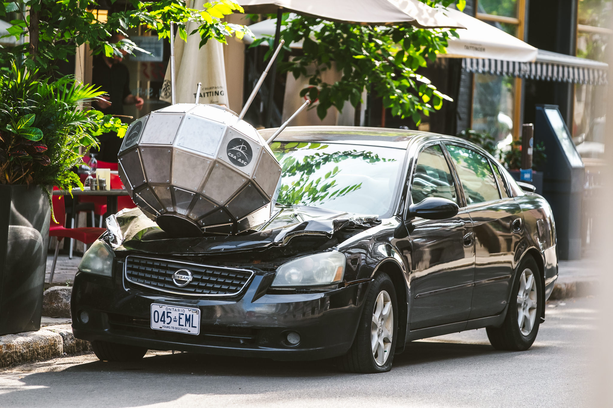 image of a black car parked on a street with a small satellite crushing the car hood.