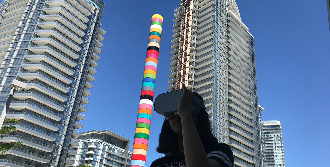 An individual standing in front of two condominiums and a large colourful pole looks through a virtual reality headset.