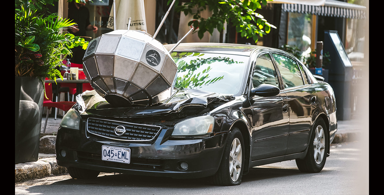Image of a parked vehicle with a satellite crashed into the hood.