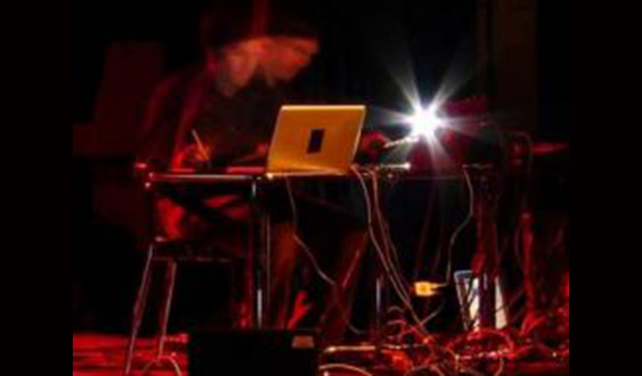 Image of Dispersion Lab Performance. Image shows person sitting behind a red lit desk with a computer.
