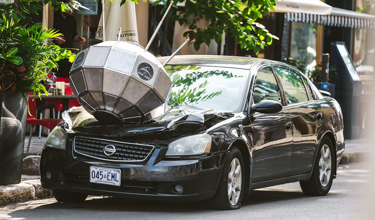 Image of a parked vehicle with a satellite with crashed into the hood.