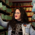 Image of Sensorium Graduate Research Associate Hillary Kaplan standing in a row of library books.
