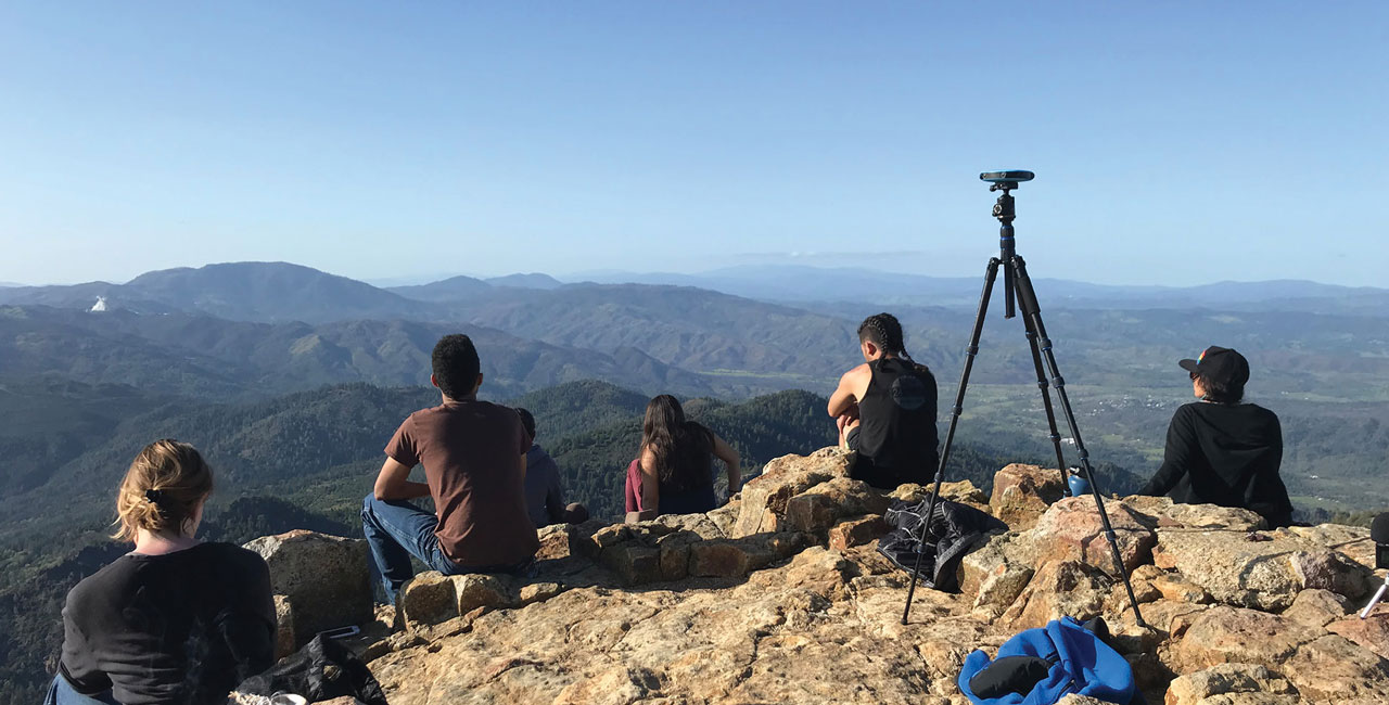 Image of group of individuals looking out over the top of a mountain.