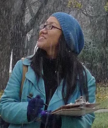 Image of Taien Ng-Chan in blue coat and hat, holding clipboard.