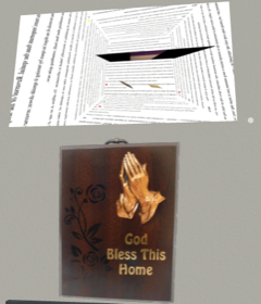 """A digital rendering of a grey wall and old fashioned plaque with praying hands and text: """"God Bless This Home."""" Above it is a large rectangle that shows a room covered in text and a black rectangle floating on the ceiling."""